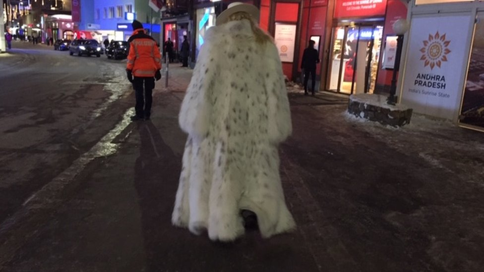 Rear view of someone in Davos wearing a fur coat