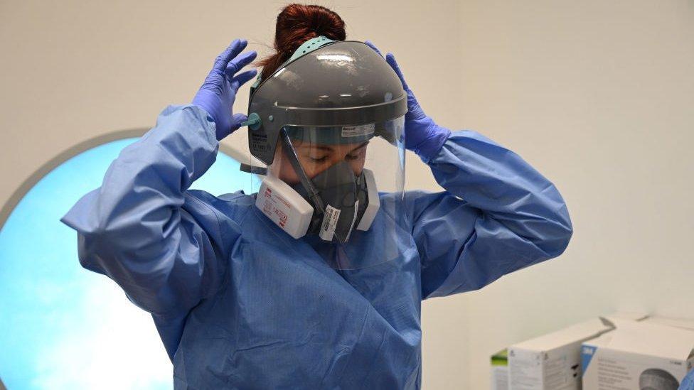 Miembro del personal clínico se pone equipo de protección personal (EPP) incluyendo una visera, máscara, bata y guantes en la unidad de Cuidados Intensivos del Hospital Royal Papworth en Cambridge, el 5 de mayo de 2020.