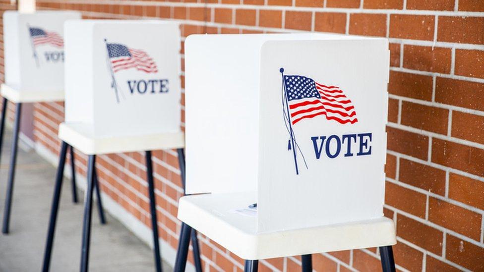 Cabinas de votación con la bandera estadounidense.