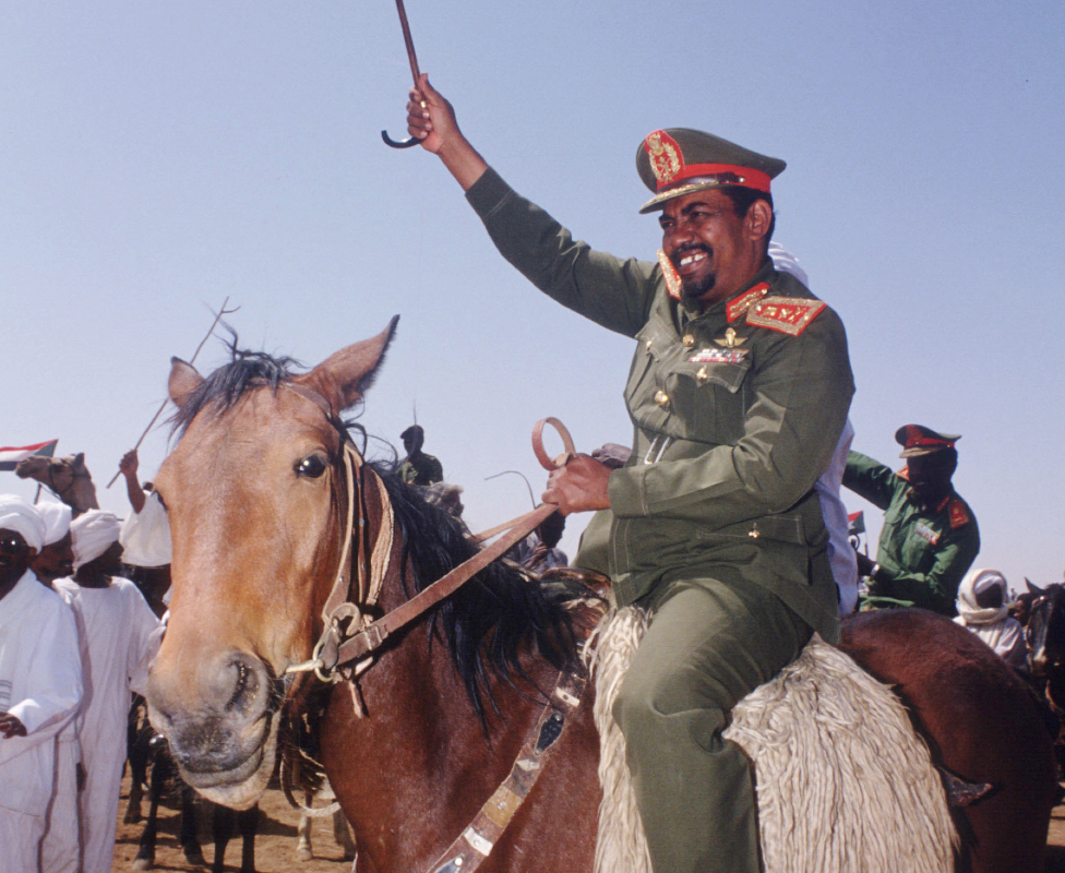 Sudan's Presdent Omar al-Bashir rides a horse greeting supporters in 1992