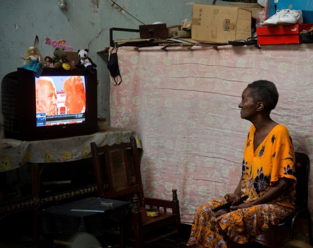 A woman in Havana watches a screen showing Donald Trump and Joe Biden graphic