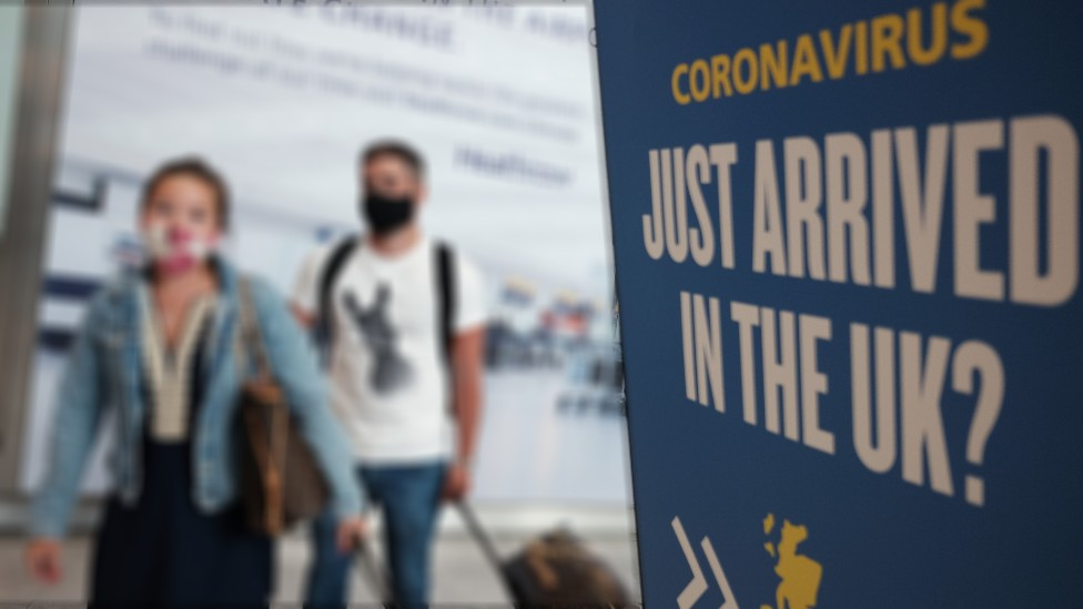 Two people in airport arrivals hall next to quarantine warning poster