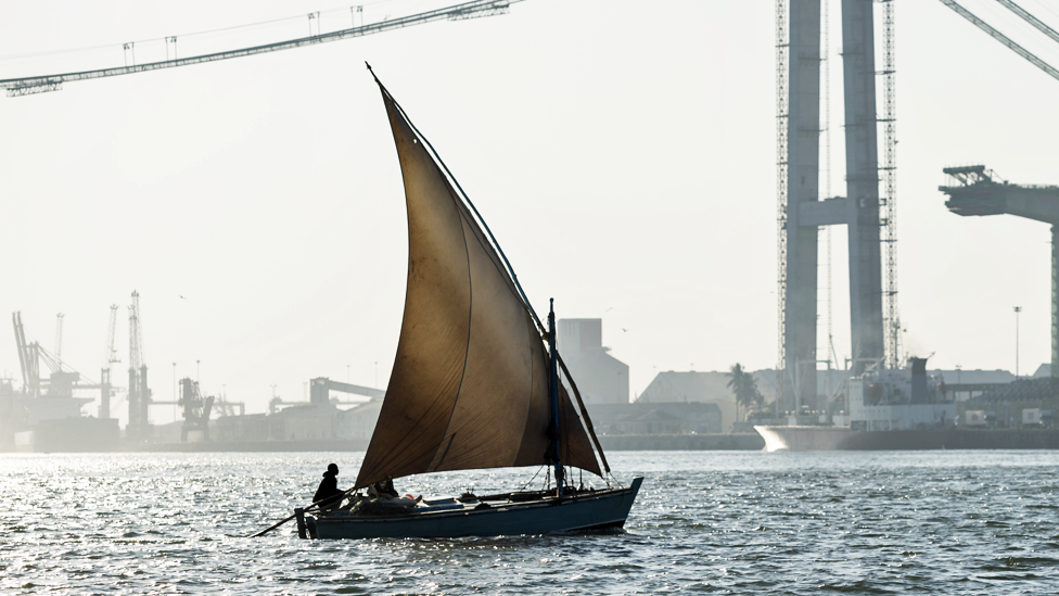 A dhow sailing in front of a Maputo road bridge